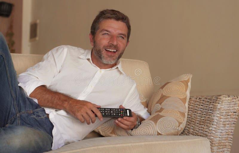 Mostra atrativa nova da televisão do homem feliz e alegre ou filme engraçado de observação da comédia que ri o telecontrole relax fotos de stock