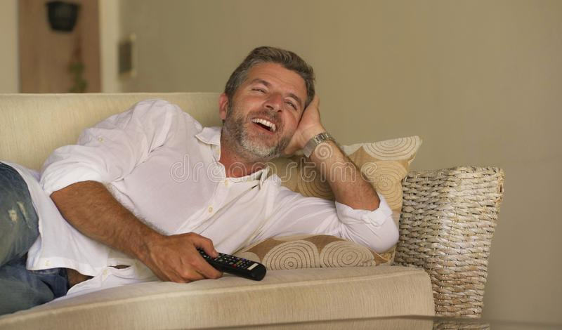 Mostra atrativa nova da televisão do homem feliz e alegre ou filme engraçado de observação da comédia que ri o telecontrole relax imagens de stock