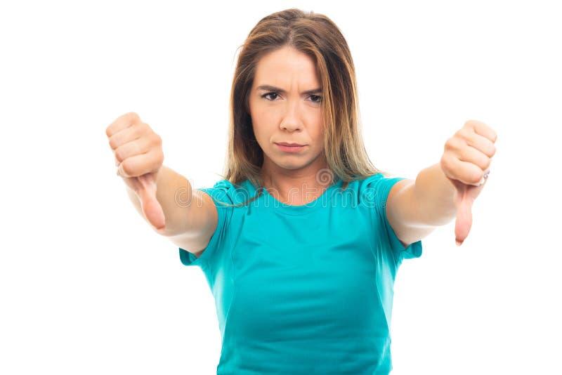 Mostra d'uso della maglietta della giovane ragazza graziosa entrambe gestur del pollice giù fotografia stock