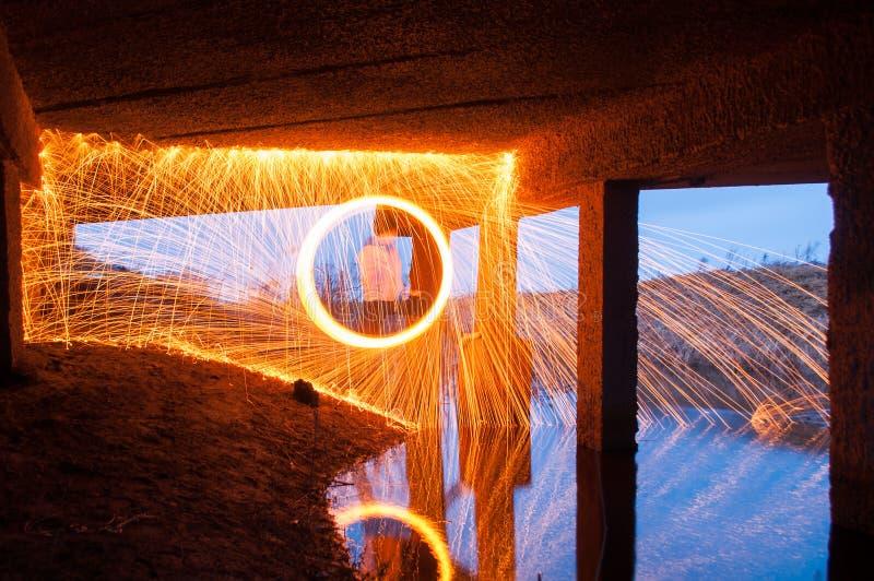 Mostra da dança do fogo Luz de palhas de aço sob a ponte fotos de stock