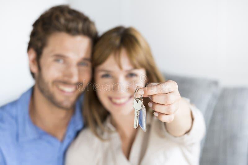 Mostra di trenta anni allegra delle coppie chiavi del loro nuovo appartamento fotografia stock libera da diritti