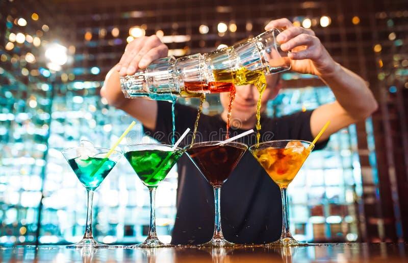 Mostra do empregado de bar O barman derrama cocktail alcoólicos na barra fotografia de stock
