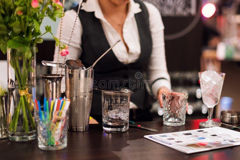 Mostra do empregado de bar O barman fêmea está fazendo o cocktail no clube noturno fotografia de stock royalty free