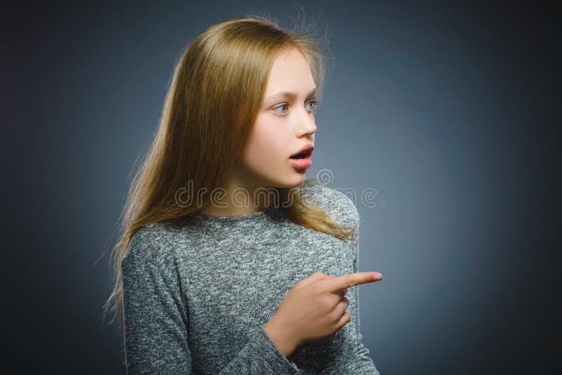 Mostra feliz da criança em algo Retrato do close up do sorriso considerável da menina fotografia de stock