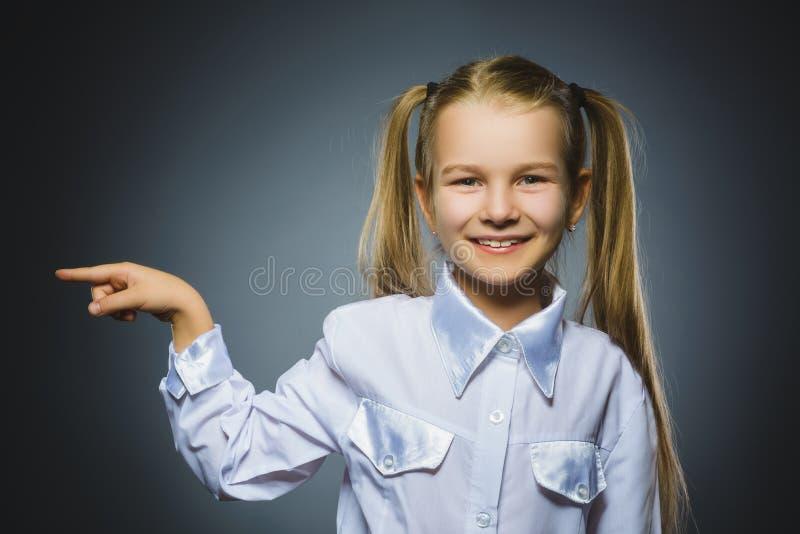 Mostra feliz da criança em algo Retrato do close up do sorriso considerável da menina imagens de stock