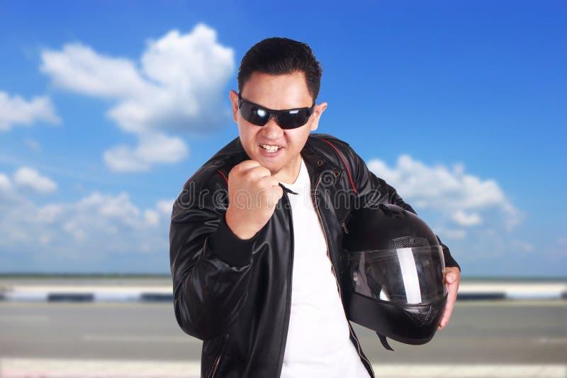 Mostra irritada do piloto do motociclista do motociclista seu punho fotografia de stock
