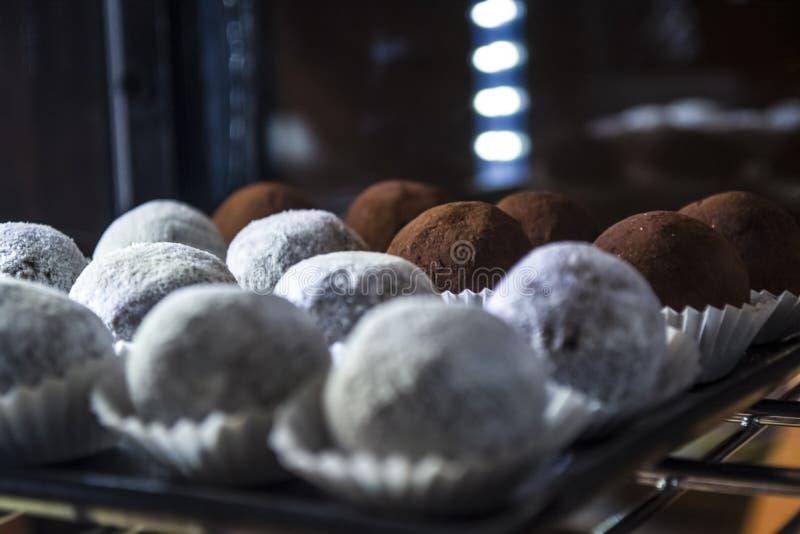 Mostra-janela de vidro com iluminação na cafetaria com os doces das bolas brancos e o chocolate Doces saborosos Bolo imagem de stock