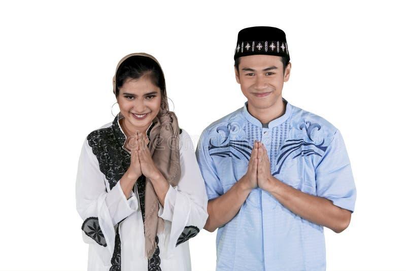 A mostra muçulmana dos pares cumprimenta o gesto de mãos no estúdio imagens de stock