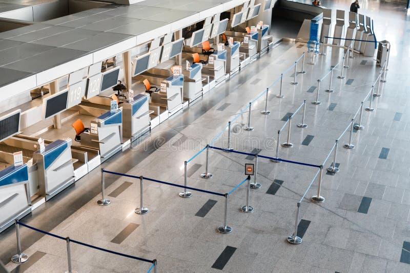 Mostradores de facturación vacíos con los ordenadores y líneas que esperan en frente en aeropuerto foto de archivo