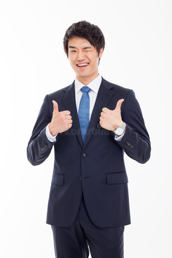 Mostrando a polegar o homem de negócio asiático novo. fotos de stock royalty free