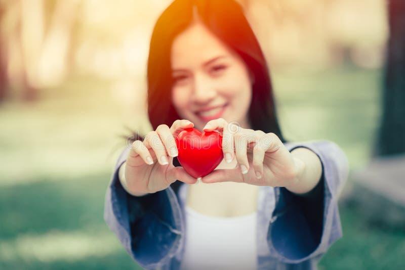Mostrar de sorriso da menina adolescente bonito dando o conceito do amor do coração foto de stock