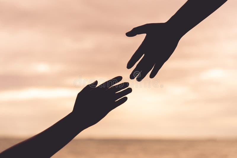 Mostre em silhueta as mãos amiga no fundo borrado do mar e do céu fotografia de stock royalty free