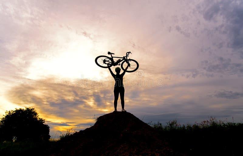 Mostre em silhueta as mulheres na bicicleta de levantamento da ação fotos de stock