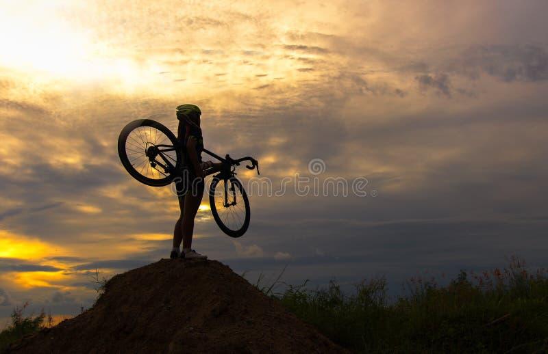 Mostre em silhueta as mulheres na bicicleta de levantamento da ação foto de stock royalty free