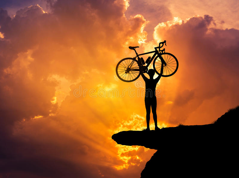 Mostre em silhueta a bicicleta de levantamento do homem acima de sua cabeça na montanha do penhasco da rocha com por do sol foto de stock royalty free
