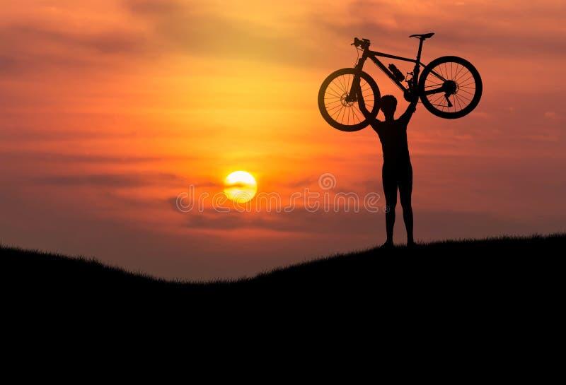 Mostre em silhueta a bicicleta de levantamento do Mountain bike do homem acima de sua cabeça no por do sol foto de stock royalty free