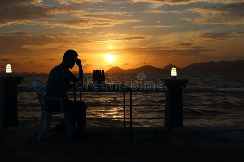 Mostre em silhueta a cerveja bebendo do homem triste na praia com sunse vermelho do céu fotografia de stock royalty free