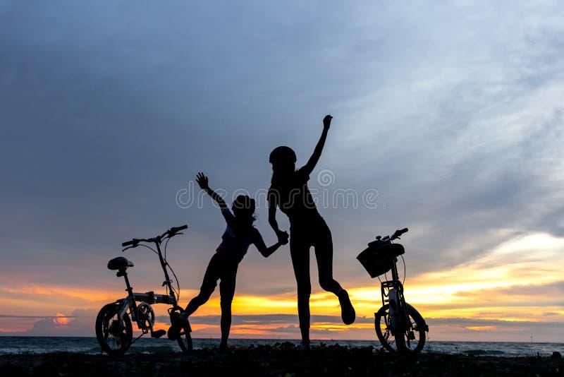 Mostre em silhueta a família bonita do motociclista da liberdade no por do sol sobre o oceano imagem de stock royalty free