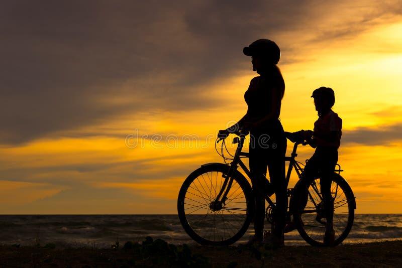 Mostre em silhueta a família bonita do motociclista no por do sol sobre o oceano Mamã e filha que bicycling na praia imagem de stock