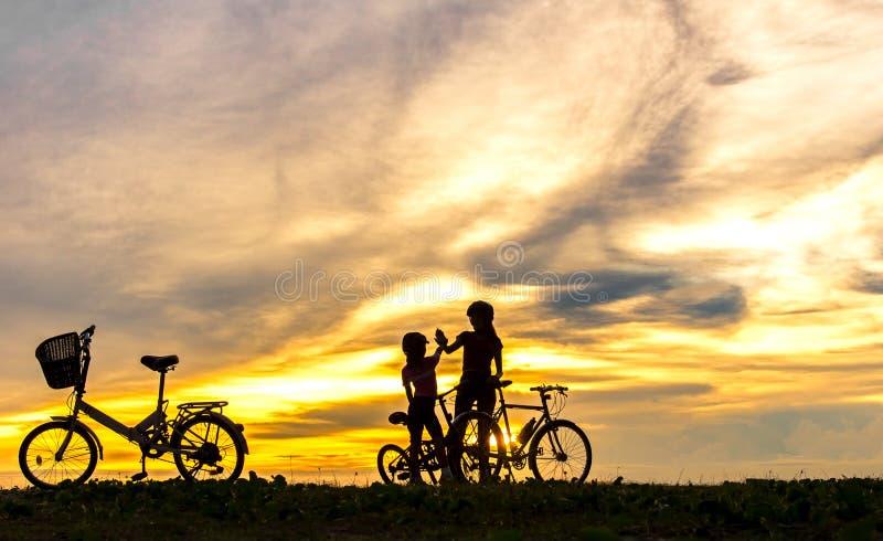 Mostre em silhueta a família bonita do motociclista no por do sol sobre o oceano Mamã e filha que bicycling na praia foto de stock