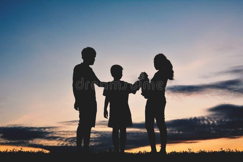 Mostre em silhueta a família e o menino que jogam com cão pequeno fotografia de stock