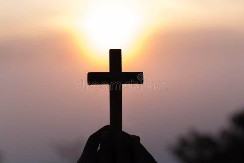 Mostre em silhueta fora das mãos que guardam a cruz de madeira no fundo do nascer do sol, crucifixo, símbolo da fé imagens de stock royalty free