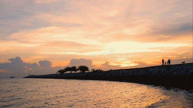 Mostre em silhueta a imagem da família feliz que anda na ponte sobre a praia fotografia de stock