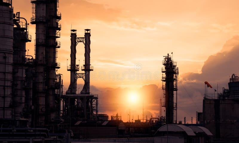 Mostre em silhueta a indústria da refinaria de petróleo e gás no fundo alaranjado do por do sol do céu imagens de stock