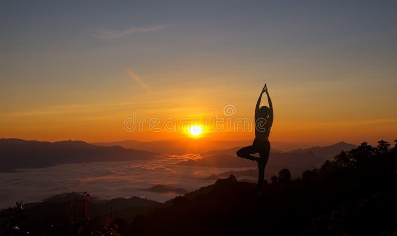 Mostre em silhueta a ioga praticando da jovem mulher na montanha no nascer do sol imagens de stock royalty free