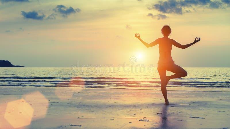Mostre em silhueta a ioga praticando da mulher na praia do mar no por do sol surrealista fotos de stock