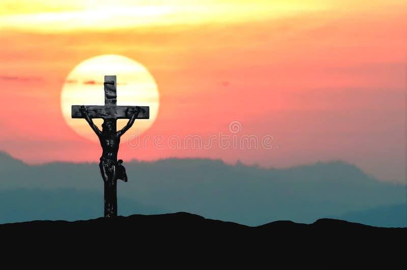 Mostre em silhueta Jesus e a cruz sobre o por do sol na montanha com espaço da cópia (a cor de água da tração da pintura) imagens de stock royalty free