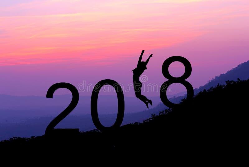 Mostre em silhueta a jovem mulher que salta sobre 2018 anos no monte na SU fotos de stock