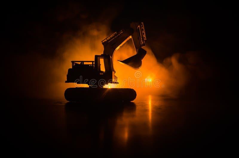 mostre em silhueta a máquina escavadora seguida no fundo alaranjado vermelho nevoento escuro do céu com carro do brinquedo Espaço imagem de stock royalty free