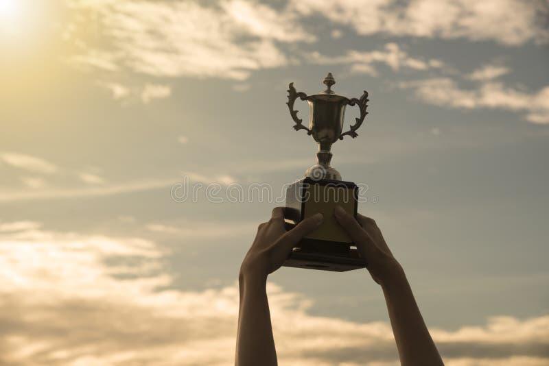 Mostre em silhueta a mão que guarda o copo do troféu do vencedor em um campeonato fotografia de stock