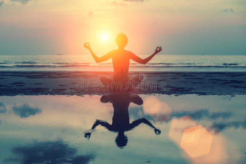 Mostre em silhueta a menina da meditação no fundo do mar e do por do sol impressionantes