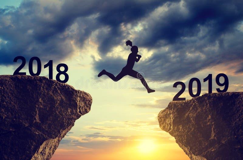 Mostre em silhueta a menina saltam ao ano novo 2019 foto de stock royalty free