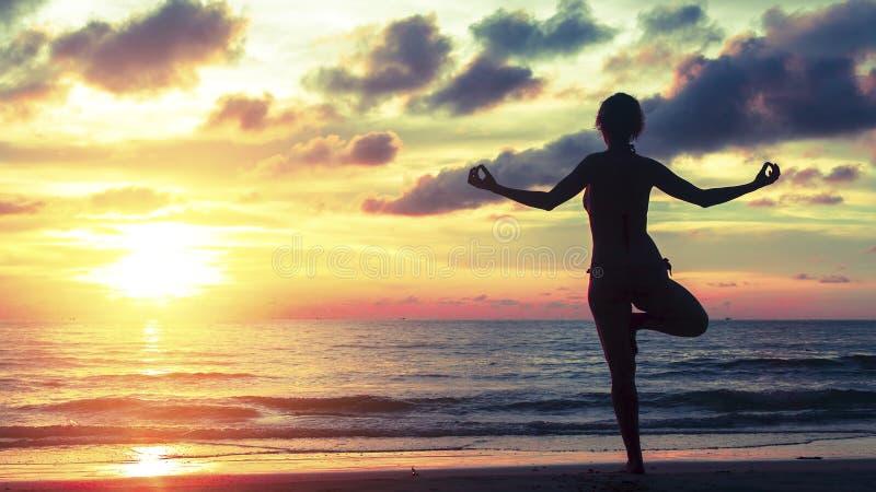 Mostre em silhueta a mulher da meditação no fundo do oceano e do por do sol surreais impressionantes fotografia de stock royalty free