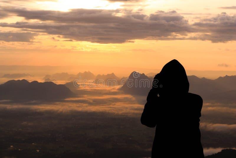 Mostre em silhueta a mulher na montanha superior na manhã foto de stock royalty free