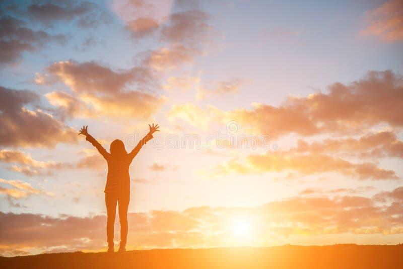 Mostre em silhueta a mulher no por do sol que está entusiasmado com braços aumentou acima a fotografia de stock royalty free