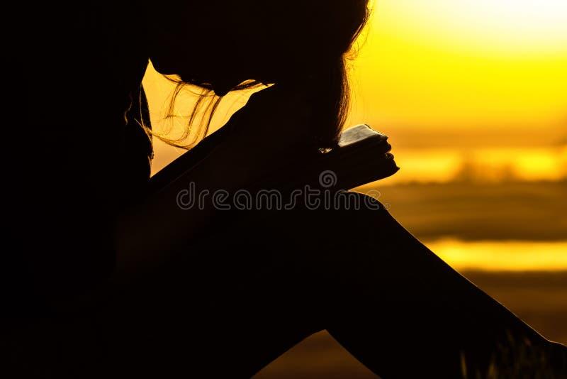 Mostre em silhueta a mulher que reza ao deus na natureza no por do sol, no conceito da religião e na espiritualidade foto de stock royalty free