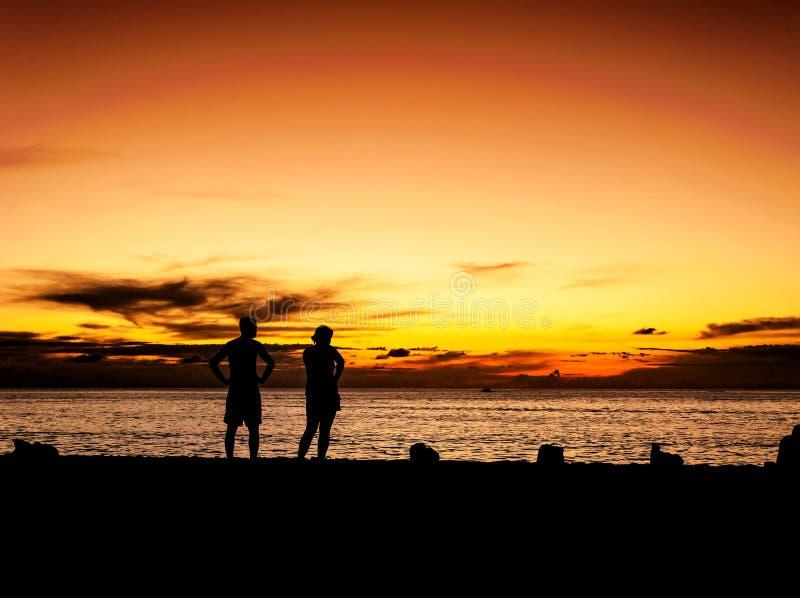 Mostre em silhueta o amante no por do sol da praia no crepúsculo imagens de stock royalty free