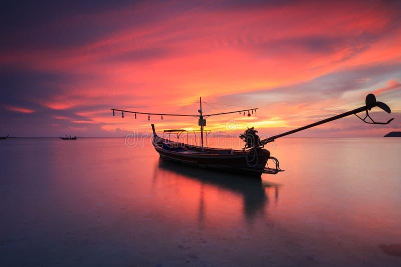 Mostre em silhueta o barco tradicional do longtail e céu vermelho bonito e s imagens de stock royalty free