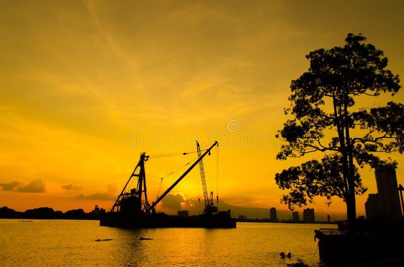 Mostre em silhueta o canteiro de obras que flutua sobre o rio com reflexão no por do sol fotografia de stock