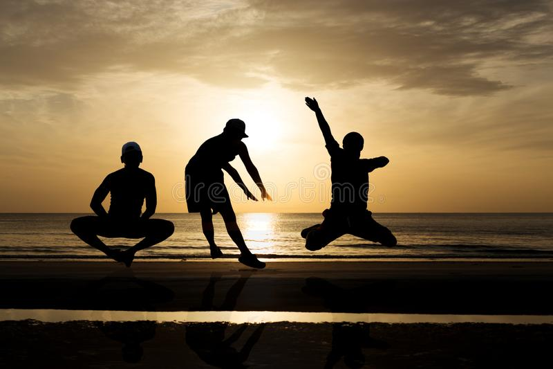 Mostre em silhueta o grupo de amigos que saltam na praia no por do sol imagens de stock