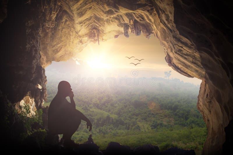 Mostre em silhueta o homem humilde que senta-se em uma rocha na caverna que olha pássaros foto de stock