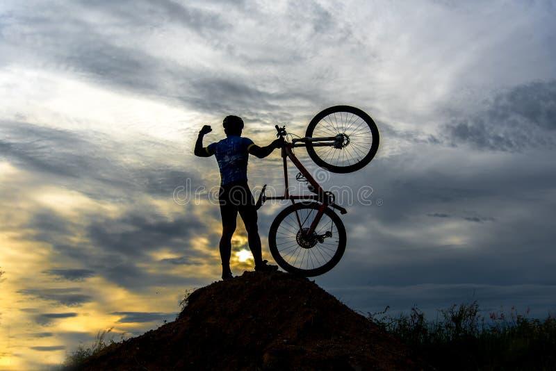 Mostre em silhueta o homem na bicicleta de levantamento da ação acima de seu suporte principal foto de stock