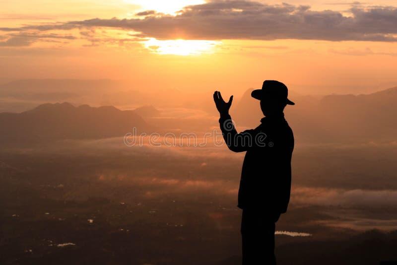 Mostre em silhueta o homem na montanha superior na manhã fotografia de stock royalty free