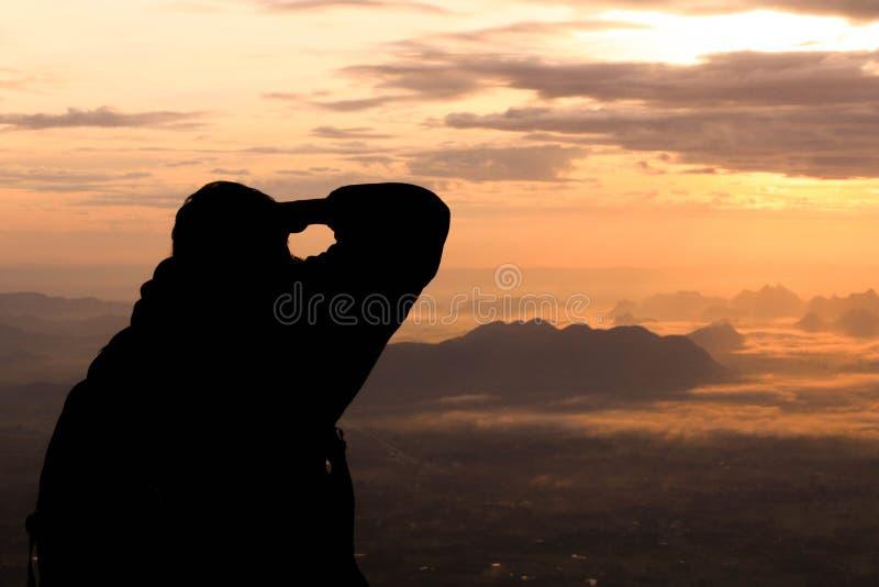 Mostre em silhueta o homem na montanha superior na manhã fotos de stock royalty free