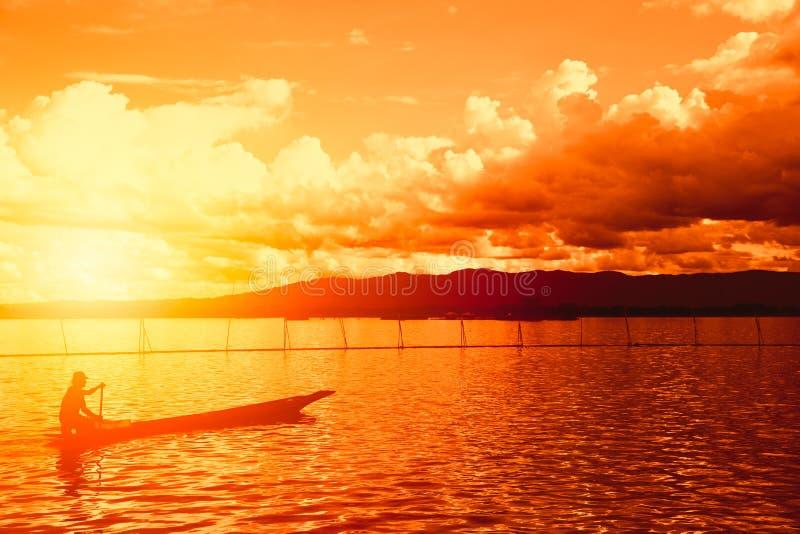 Mostre em silhueta o homem no barco de madeira com por do sol bonito imagem de stock royalty free