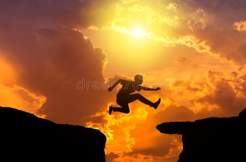 Mostre em silhueta o homem que salta com a diferença sobre o penhasco da rocha entre a montanha no por do sol fotografia de stock royalty free
